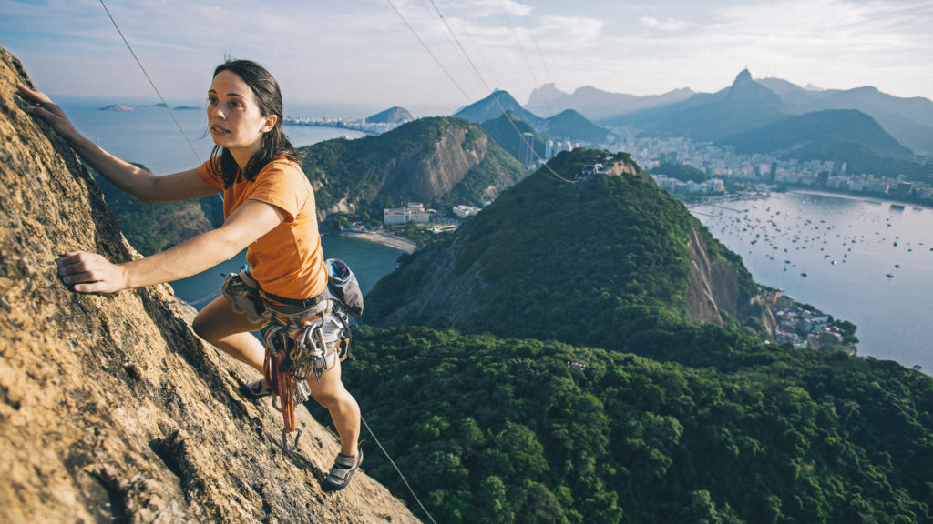 Rock climbing on Sugar Loaf (Rio) with the statue of the Christ the Redeemer in the background. (Photo by Olivier Renck/Cavan Images.)